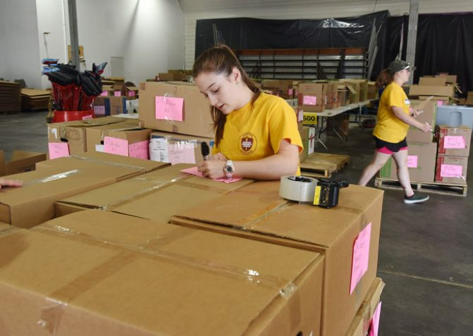 woman labeling cardboard boxes in warehouse